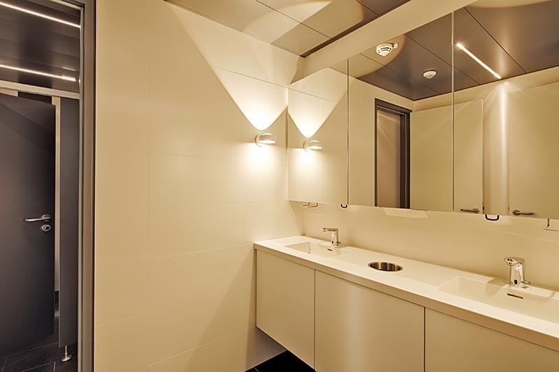 Auch die WCs sind in die Lichtplanung integriert. Speziell entworfene Lichtlinien, geben ein Allgemeinlicht ab. In den Vorräumen geben wohnliche Occhio-Leuchten ein direkt / indirektes Licht und nehmen so Bezug auf das Gesamtkonzept der Lichtarchitektur. Foto: Planlight GmbH