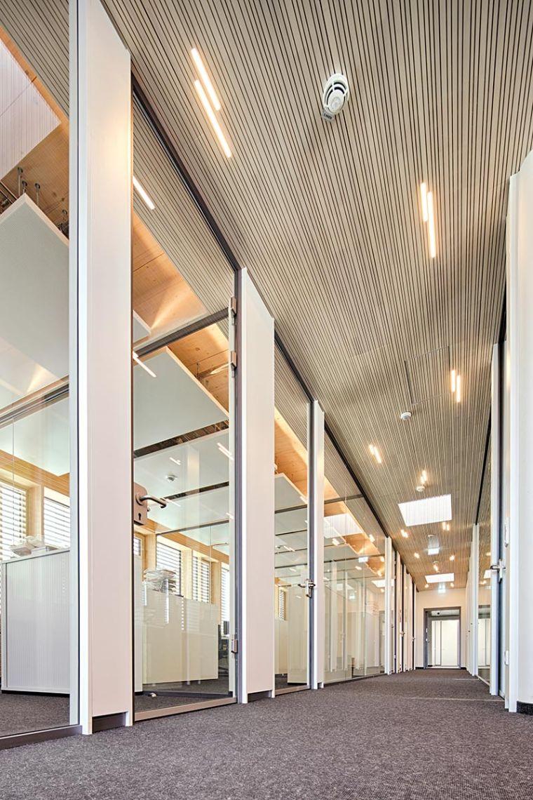 In die akustisch wirksame Holzpaneeldecke des Flures wurden kurze Lichtlinien eingepasst. Was wie zufällig hingeworfen aussieht, ist sorgfältig geplant: das gesamte Beleuchtungskonzept ist DIN-konform umgesetzt und zeigt dabei, wie spannend gute und individuelle Lichtarchitektur sein kann. Foto: Planlight GmbH