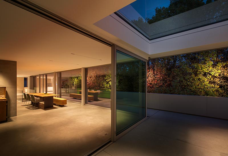 Ein Teil der ehemaligen Wohnung wird nun als überdachte Terrasse genutzt. Der gespachtelte Estrich im Innenraum scheint mit den Betonfliesen auf der Terrasse zu verschmelzen. Das Esszimmer wird von warmem Licht geringer Intensität durchflutet. Je nach Tageszeit und Tageslichteintrag verändert sich die Lichtintensität automatisch. Foto: David Franck, Stuttgart