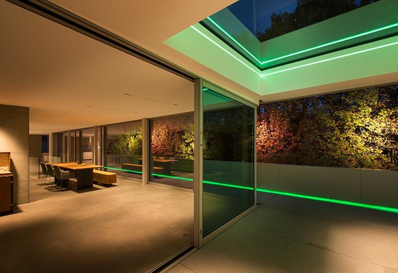 Underscore-Lichtlinien mit RGB-Technologie inszenieren den Außenbereich mit farbigem Licht. Eine Linie folgt den Konturen des quadratischen Oberlichts im überdachten Terrassensegment. Eine weitere wurde geschickt am unteren Abschluss der Corian-Verkleidung der Brüstung montiert. Man sieht nur das Licht, nicht die Leuchte. Foto: David Franck, Stuttgart