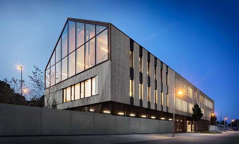 Markant erhebt sich der moderne Gewerbebau von w:architekten inmitten des Freudenstädter Bahnhofsviertels. Die Holzlamellenverschalung und das aus dem Innenraum strahlende behagliche Licht geben der Beton-Kubatur Wärme. Bild: Steffen Schrægle Photography, Hallwangen