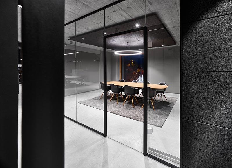 Akustikelemente, welche die Architekten schwarz übermalen ließen, absorbieren im Besprechungsraum den Schall. Bündig eingebaute, justierbare Diro-Strahler von Delta Light beleuchten die Umgebung des Besprechungstisches. Der Tisch selbst wird von einer großen Super-OH!-Ringleuchte erhellt, die gleichzeitig ein Highlight setzt. Bild: FOTOGRAFIE FREI, Ostfildern