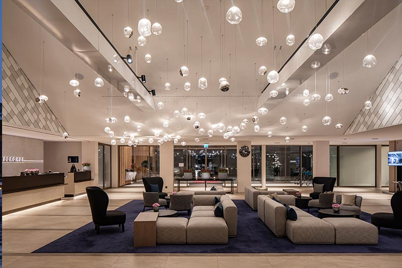 Die Mehrkomponenten-Beleuchtung, die Notholt Lighting Design für die Lobby plante, besteht aus dezenten Architekturleuchten von iGuzzini und einer individuell gefertigten Schwarm-Installation, welche die Lichtplaner gemeinsam mit JOI-Design und einem Hersteller hochwertiger Glas-Sonderleuchten entworfen haben. Foto: Felix Löchner für iGuzzini