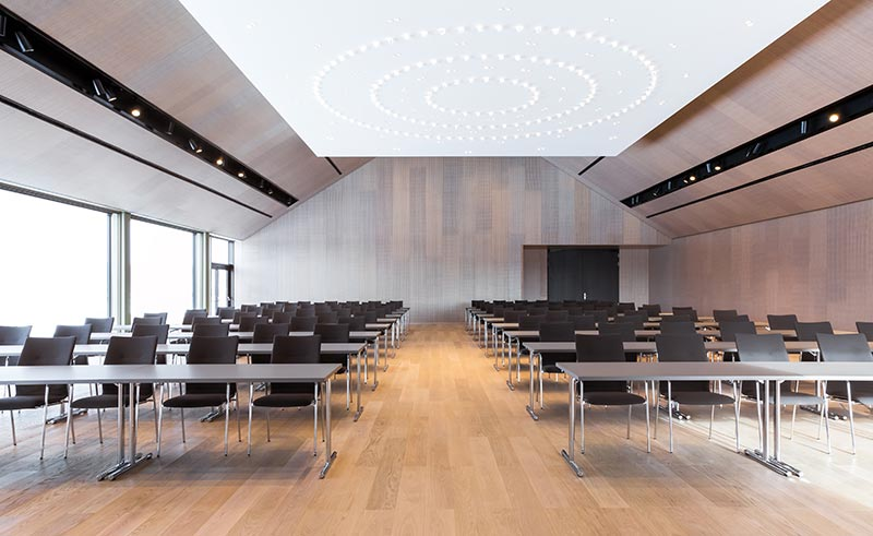Der 400 qm große Bankettsaal ist das Highlight des neuen zweigeschossigen Konferenzzentrums. Der verfahrbare akustisch wirksame Plafond ist mit kleinen Laser-Strahlern bestückt, deren Lichtszenarien auf die unterschiedlichen Bestuhlungsmöglichkeiten abgestimmt sind. Zusätzliche Glasleuchten sorgen für ein dekoratives Moment. In den seitlichen Deckenkanälen ergänzen Palco-Strahler die Beleuchtung. Foto: Der Öschberghof