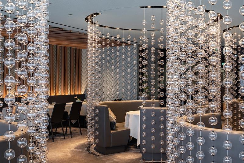 Kleine Laser-Downlights lassen die Glaskugelvorhänge im Edel-Restaurant Ösch Noir zauberhaft funkeln. Je ein weiteres Laser-Downlight beleuchtet zentral die Tische. Die dezente Beleuchtung unterstreicht die Wertigkeit und zeigt sich auch in der Außenansicht stimmungsvoll. Foto: Felix Löchner für iGuzzini
