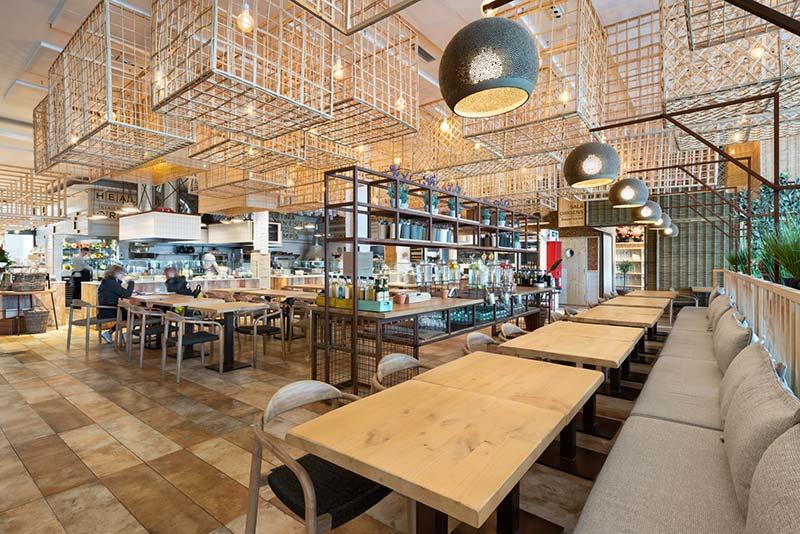 """Im """"CoMMons"""" speisen täglich rund 400 Gäste, zusätzlich gehen etwa 300 Take-away-Gerichte über die Theke. Die modular aufgebauten Gerichte aus Produkten des Hauses werden vor den Augen der Gäste in einer zentralen, offenen Küche zubereitet. Foto: BÄRO/Constantin Meyer"""