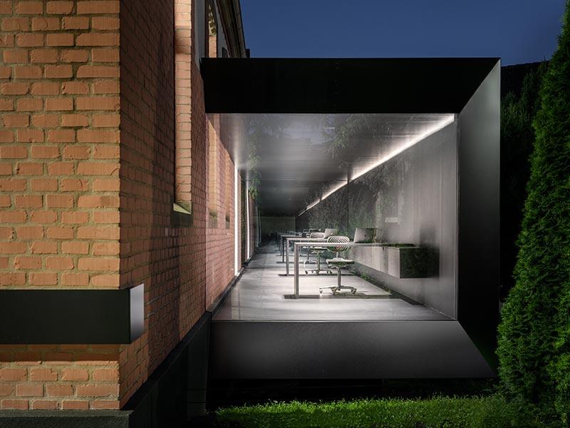 Der schwebende, schwarz gehaltene Anbau aus Holz mit verglasten Stirnseiten gibt den Blick auf das Bestandgebäude frei. Eine Underscore-Leuchte sorgt für auch farbig gestaltbares Effektlicht (RGB). Bildquelle: David Franck, Stuttgart