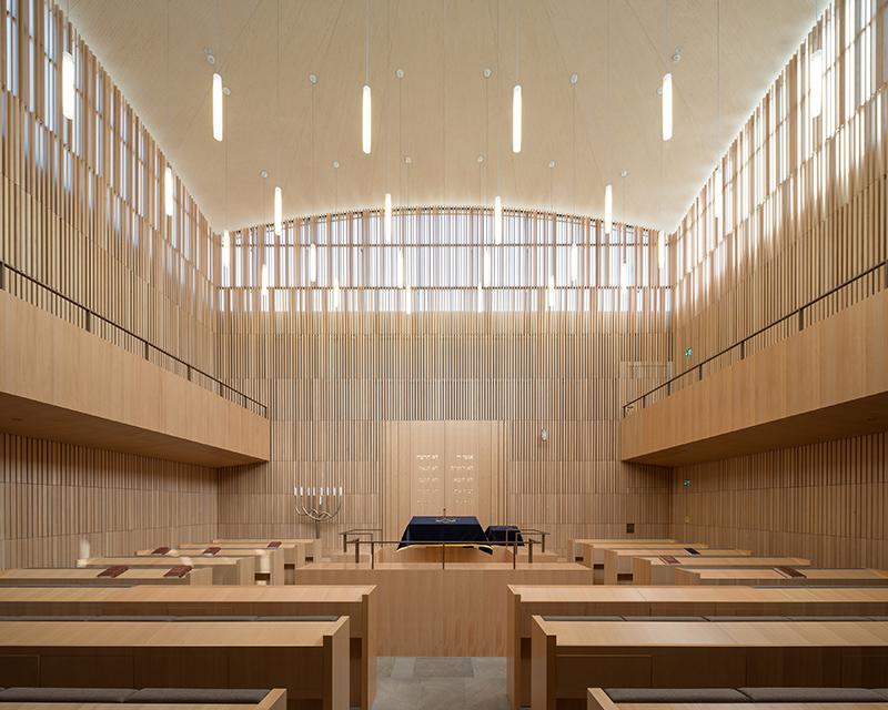 In der 1. Etage befindet sich der zweigeschossige Synagogenraum mit seiner Empore. Am Übergang von der Wand zur flachen Holzkuppel befindet sich ein Fensterband, das die Synagoge angenehm mit Tageslicht auflädt. Bildquelle: Marcus Ebener