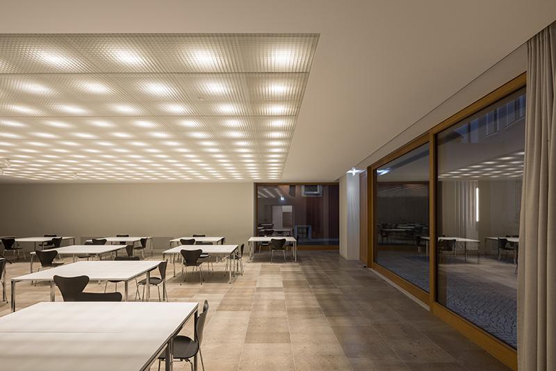 Die Leuchten in der Kassettendecke des Gemeindesaals im Erdgeschoss sorgen für die allgemeine Helligkeit im Raum und geben den vertikalen Flächen der darunter angeordneten Gitterdecke eine weiche Lichtpräsenz. Bildquelle: Marcus Ebener