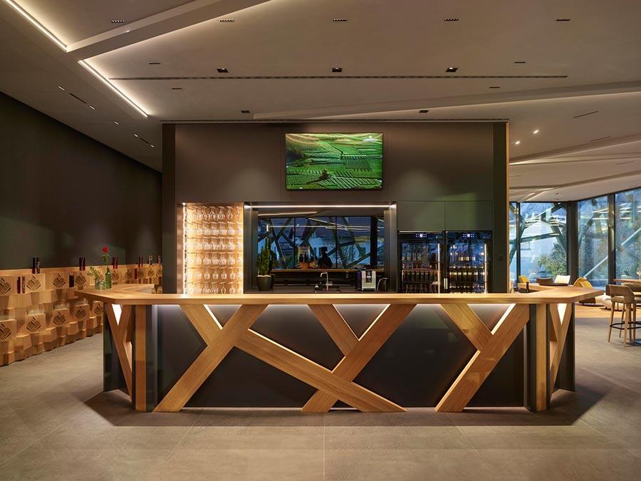 Die Gestaltung der Bar ist ebenfalls von Sarment inspiriert. Im Licht der Laser Blade-Downlights erscheinen die Holztöne besonders warm. Bildquelle: Roland Halbe